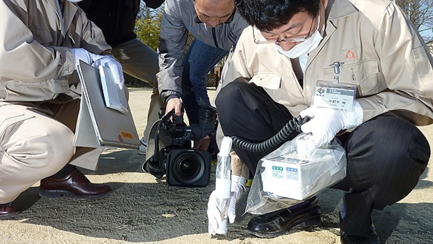 April 5: Prefectural government's employees monitor amount of radiation on the ground of an elementary school in Fukushima, northern Japan.