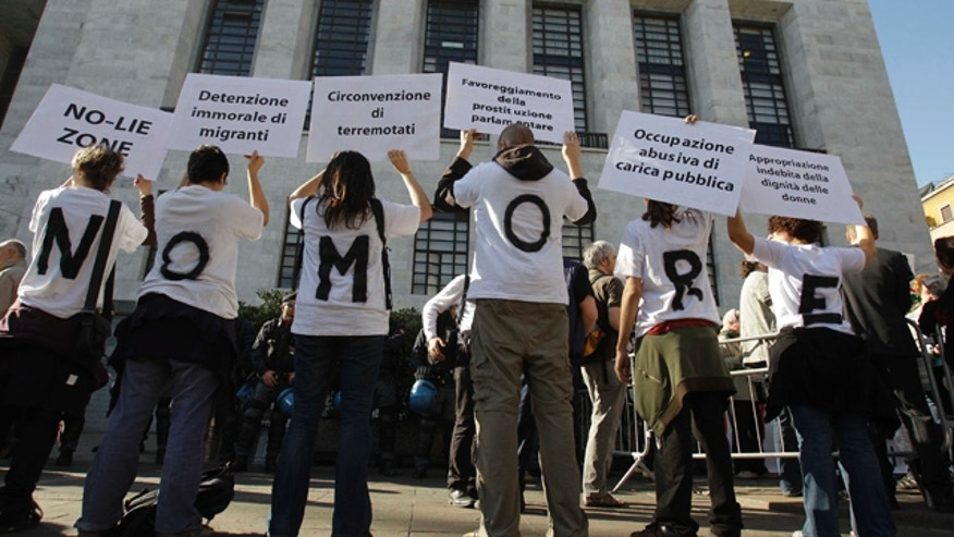 "April 6: People wear t-shirts composing the sentence ""No more"" as they hold up placards during a protest outside the Milan court in Italy."