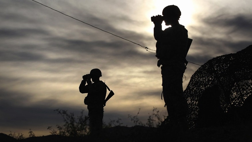 Arizona National Guardsmen watch over the U.S. border with Mexico at an observation post on December 7, 2010 in Nogales, Arizona.