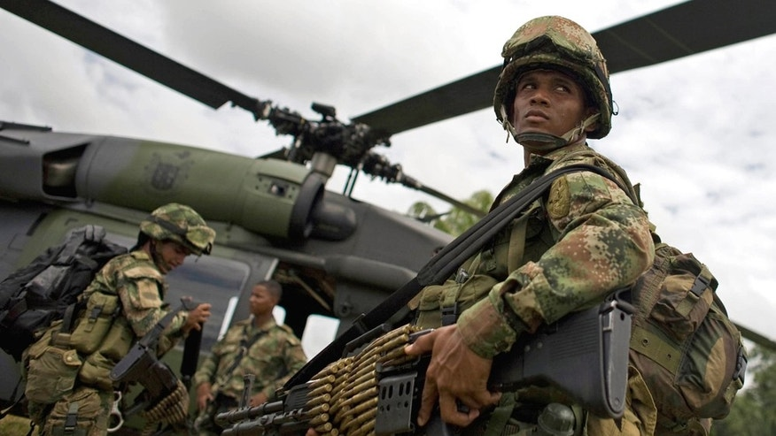 Soldiers board a helicopter in Guerima, in the eastern province of Vichada, Colombia, Wednesday March 9, 2011.  (AP Photo/William Fernando Martinez)