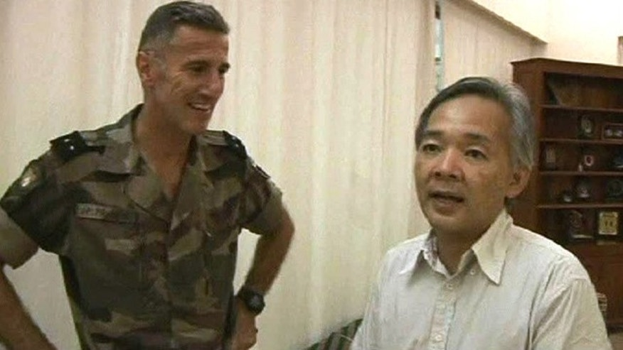 April 7: This image taken from a video provided by the French military shows Yoshifumi Okamura, right, the Japanese ambassador to Ivory Coast thanking an unidentified French officer of the Licorne operation, left, following a rescue mission to airlift the ambassador to safety in Abidjan, Ivory Coast.