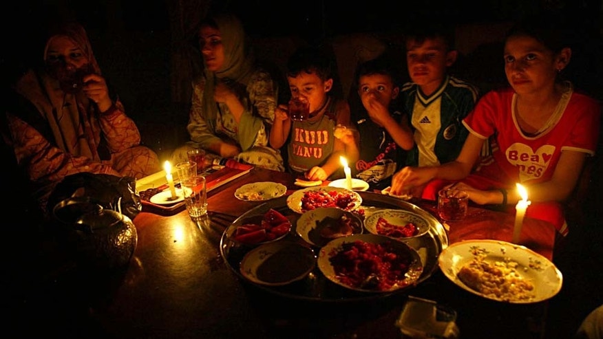GAZA CITY, GAZA STRIP - AUGUST 21:  A Palestinian family eats dinner by candle light during a power outage August 21, 2007 in Gaza City, Gaza. The European Union announced that it will resume fuel aid to the Gaza Strip's electric company ending the aid suspension that began amongst suspicions that Hamas was planning to tax the sale of electricity to fund its government in the territory.  (Photo by Abid Katib/Getty Images)