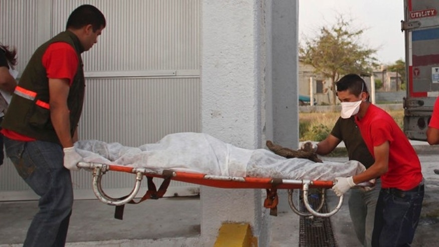 April 7: Morgue employees take a body, found on Wednesday in a mass grave, from a refrigerated truck into the local morgue in Matamoros, northern Mexico.