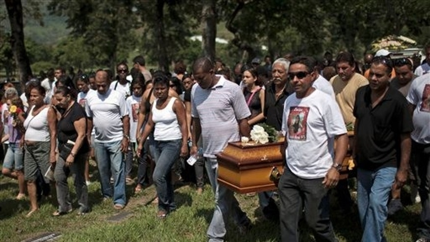 April 8: Mourners carry  for burial the coffin containing the remains of 14-year-old Luiza Paula da Silveira Machado at a cemetery in Rio de Janeiro, Brazil. Brazilian families began burying the 12 children gunned down in the halls of their elementary school Thursday. (AP)