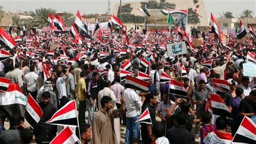 April 9: Followers of radical Shiite cleric Muqtada al-Sadr wave Iraqi flags during a rally marking the eighth anniversary of the fall of the Iraqi capital to American troops in Baghdad, Iraq. A powerful anti-American Shiite cleric has threatened to reactivate his feared militia in Iraq if U.S. soldiers extend their stay. (AP)