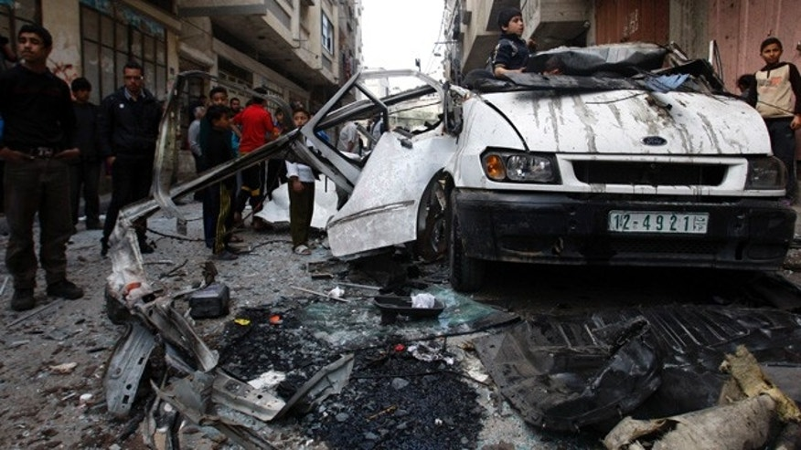 April 9: Palestinian children gather next to a car destroyed in an Israeli strike on Gaza City.