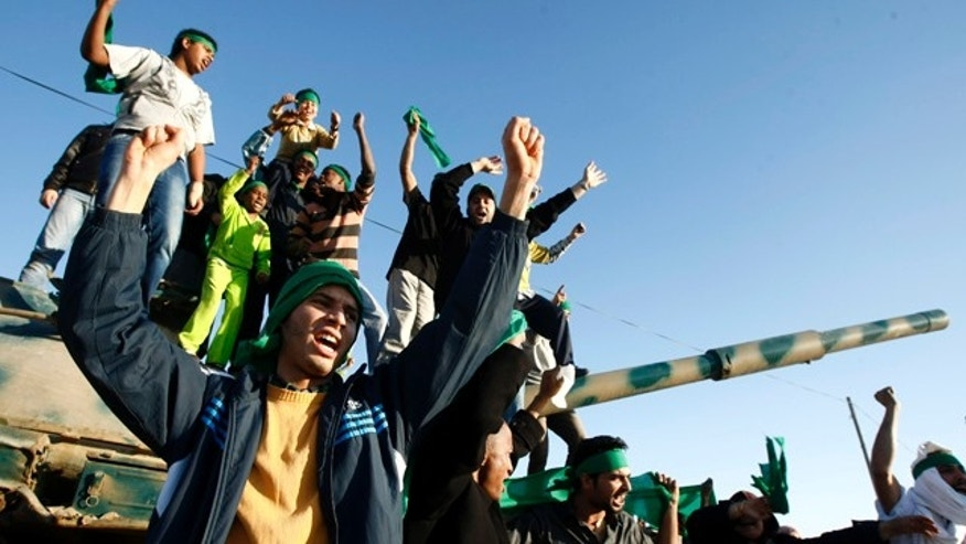 April 8: In this photo taken during a trip organized by Libyan authorities, Libyan youth wave their national flags and chant pro-Libyan leader slogans in the outskirts of the coastal city of Misrata.