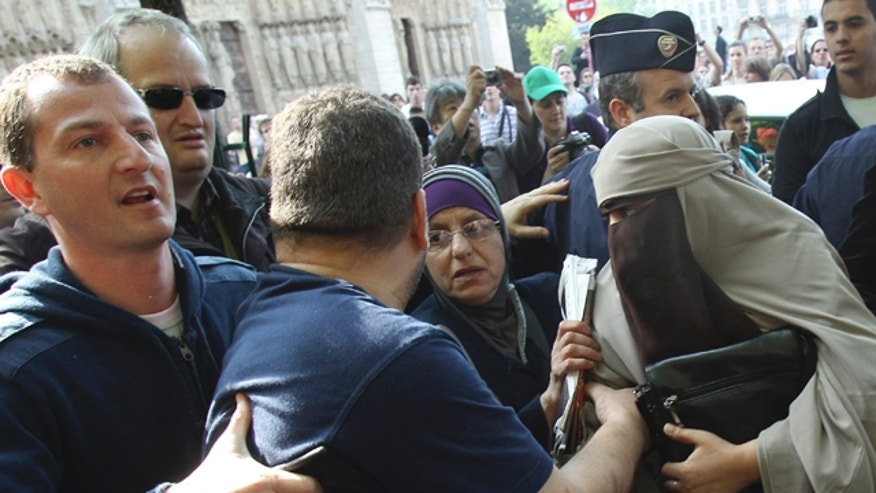 April 11: An unidentified veiled woman, right, is taken away by plain clothed police officers, left and second left, as she is accompanied by two friends, center left and right, in Paris. France's new ban on Islamic face veils was met with a burst of defiance Monday, as several women appeared veiled in front of Paris' Notre Dame Cathedral and two were detained for taking part in an unauthorized protest. France on Monday became the world's first country to ban the veils anywhere in public. (AP)