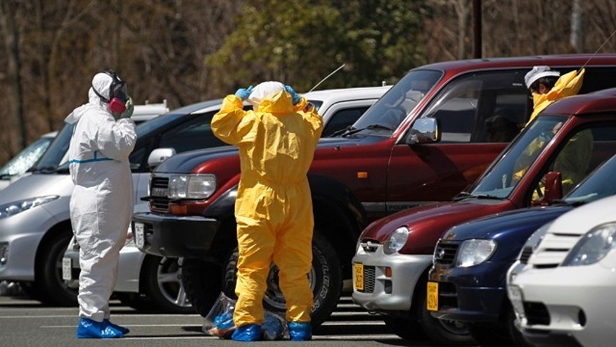 April 12: People put on radiation protect suits in a parking lot of J-Village in Naraha, Fukushima Prefecture, northeastern Japan. J-Village was a sports complex which has been converted to a base for workers at the tsunami-damaged Fukushima Dai-ichi nuclear plant. (AP)