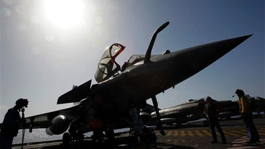 April 13: Mechanics works on a Rafale fighter jet before a mission over Libya from France's flagship Charles de Gaulle aircraft carrier, in the Gulf of Sirte, off the Libyan coast. The missions are aimed at enforcing the no-fly zone and suppressing any attacks by Gadhafi's forces against civilians and rebels in eastern Libya. (AP)