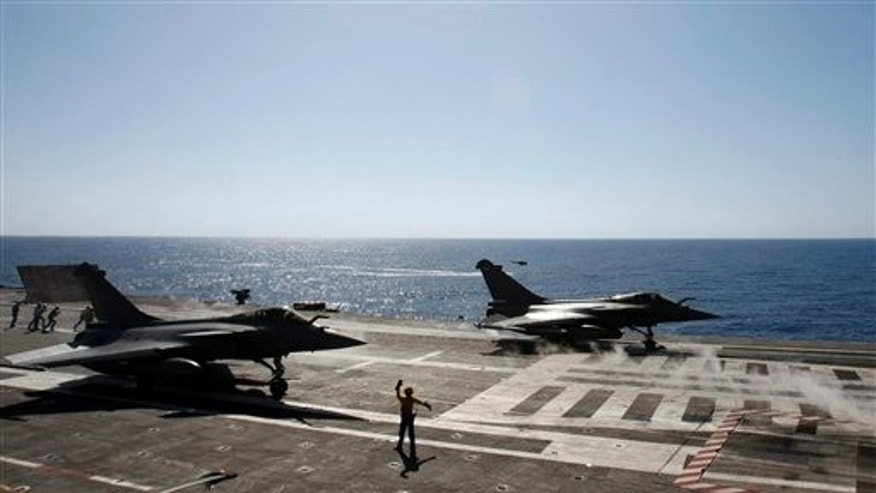 April 12: Rafale fighter jets take off for a mission over Libya to France's flagship Charles de Gaulle aircraft carrier, in the Golf of Sirte, off the Libyan coast. The missions are aimed at enforcing the no-fly zone and supressing any attacks by Gadhafi's forces against civilians and rebels in eastern Libya. (AP)