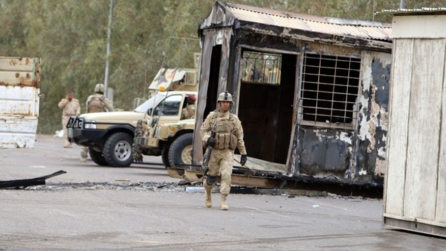 April 8: Iraqi Army soldiers stand guard near burned trailers at Camp Ashraf north of Baghdad, Iraq.