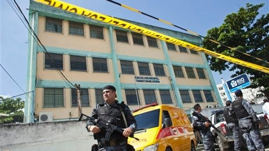 Police guard the perimeter of a school after a shooting in Rio de Janeiro, Brazil, Thursday April 7, 2011.  Brazilian authorities say that a gunman opened fire in the elementary school and at least 13 people are dead, including the gunman.  (AP Photo/Victor R. Caivano)