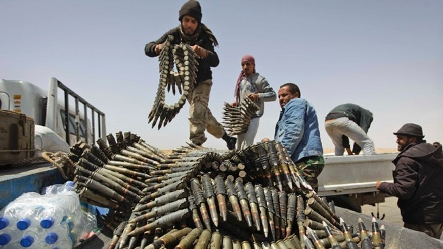 April 16, 2011: Libyan rebel fighters load a truck with ammunition on the outskirts of Ajdabiya, Libya