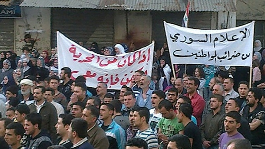 April 17: In this citizen journalism image made on a mobile phone and acquired by the AP, Syrian anti-government protesters hold Arabic banners that read: 'Syrian media from the taxes of the citizens,' right, and 'If the price of freedom is a shroud, it is with me,' as they march during a demonstration in Banias, Syria.