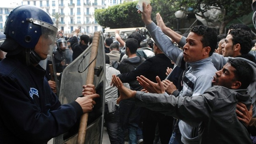 April 12, 2011: Students react to a police officer during a protest in Algiers, as thousands march to demand the resignation of the education minister in the latest anti-government protests to sweep across the Arab world. The students are defying a longtime ban on protests in Algiers, a measure adopted at the height of Algeria's Islamic insurgency and were blocked by police while trying to reach the government's headquarters.