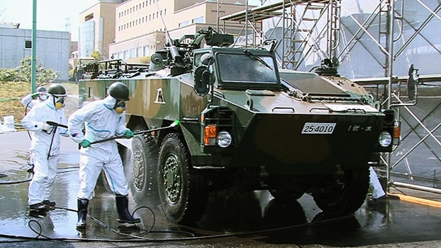 April 12: In this photo released by the Japan Defense Agency via Kyodo News, Japanese soldiers wash an armored vehicle to remove potential radiation contamination at J-Village, a soccer training complex now serving as an operation base for those battling Japan's worst nuclear disaster, northeastern Japan.