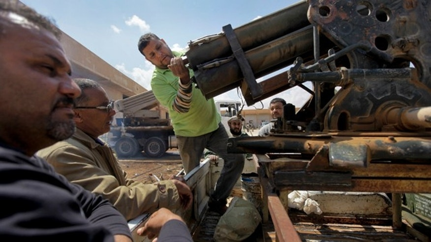 April 19: Workmen prepare a Grad rocket launcher for operation at a Libyan rebel weapons workshop and training camp in Benghazi, Libya.