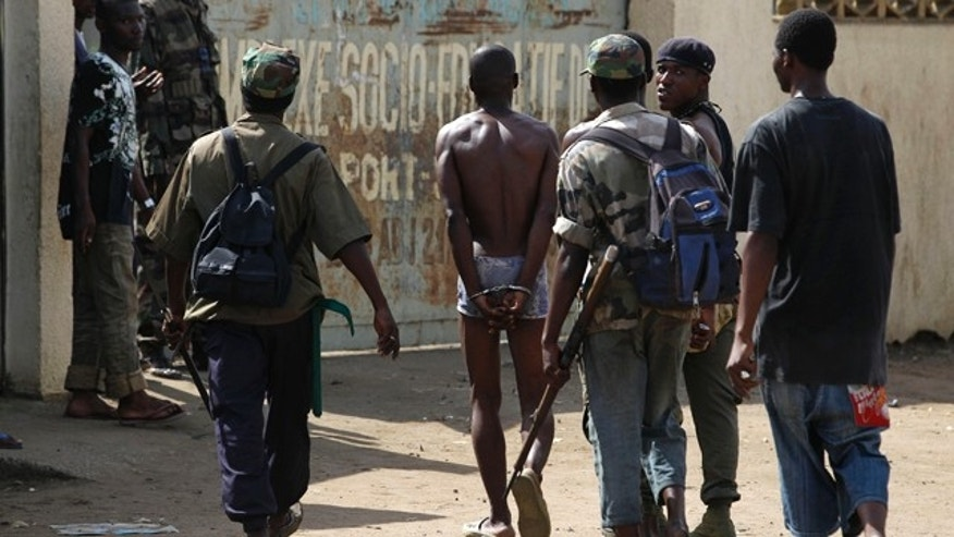 April 19: Republican forces soldiers lead a handcuffed alleged militiaman loyal to Laurent Gbagbo into a social center where thousands have sought refuge from fighting in the Youpougon neighborhood, in Abidjan, Ivory Coast.