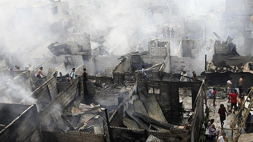 April 19: Informal settlers rummage through the still-smoldering debris following a fire that razed close to a thousand shanties at Makati city, the country's financial district, east of Manila, Philippines.