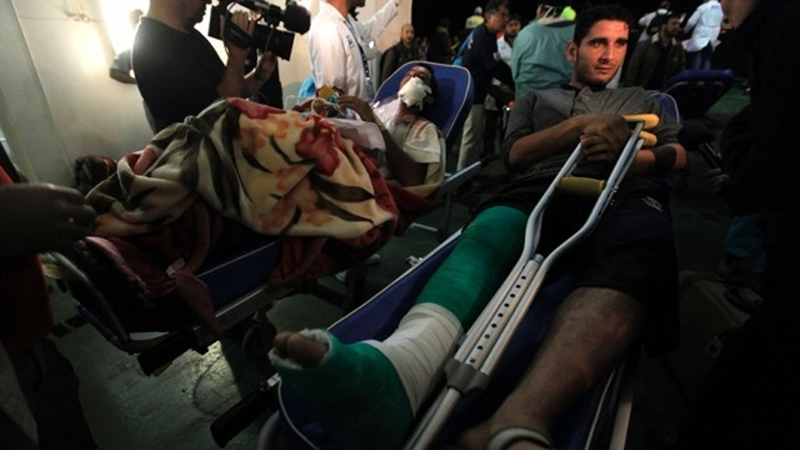 April 18: Two injured Libyan men are moved toward a waiting ambulance outside a boat that evacuated foreign refugees and injured residents, who were trapped for weeks by the fighting in Misrata, and docked at the port of Benghazi, Libya.