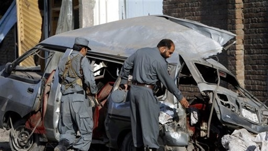 April 21: Afghan police officials investigate a damaged vehicle at the site of an explosion in Jalalabad, Nangarhar province east of Kabul, Afghanistan.