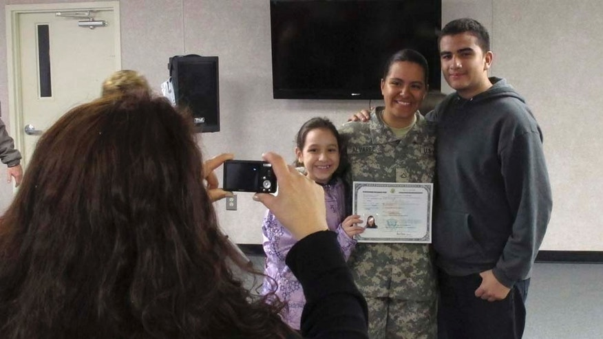 In a March 16, 2011 photo, Army Pfc. Jennifer Alvarez, center, of Colombia, poses with her family after taking the oath to become a U.S. citizen, at Fort Jackson, S.C. Military service has long been one route to U.S. citizenship. Now the Army and Navy, in need of specialists and language skills, are speeding things up by allowing recruits to wrap up the process while they're still in basic training. (AP Photo/Jeffrey Collins)