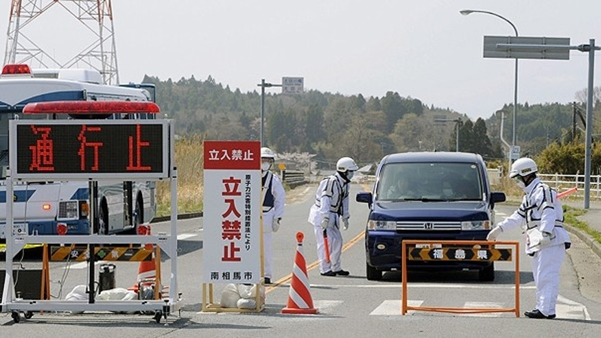 April 21: Police officers man a checkpoint with a placard reading, 'Off Limits,' at Minami Soma, Fukushima prefecture, as a vehicle with residents passes by to evacuate from the city.