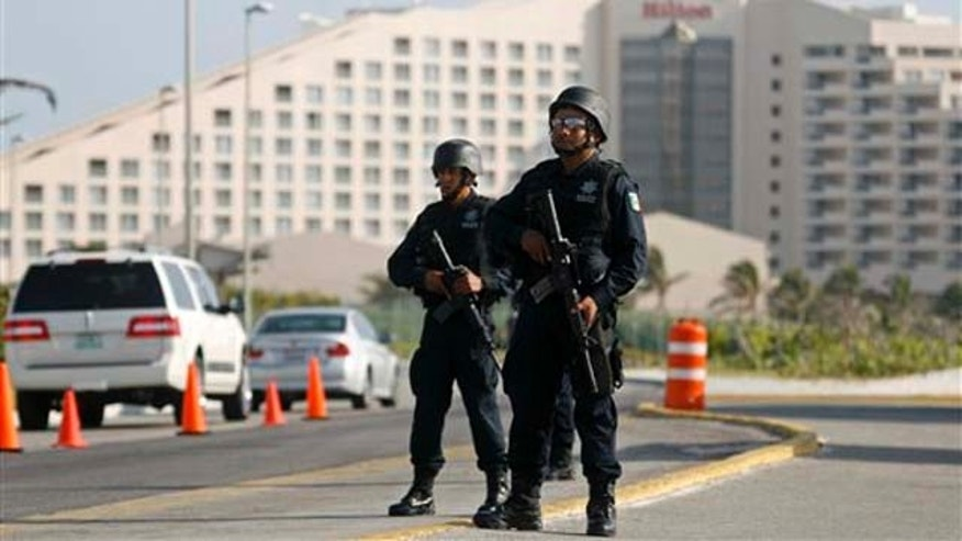 Mexican federal police officers stand in guard during the International Drug Enforcement Conference (IDEC) in Cancun, Mexico , Wednesday  April. 6, 2011. (AP Photo/Israel Leal)
