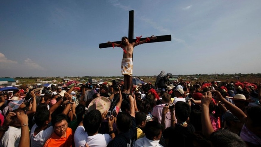 April 22: A crowd watches as Victor Caparas takes part in a reenactment of the crucifixion of Jesus Christ on Good Friday at Cutud village, San Fernando city, Pampanga province, northern Philippines. Several Filipinos were nailed to wooden crosses Friday to reenact Jesus Christ's suffering in an annual rite that has been rejected by Catholic church leaders but draws thousands of tourists on Good Friday. (AP)