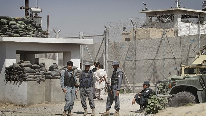 April 25: Afghan policemen stand in front of gate of the main prison in Kandahar, south of Kabul, Afghanistan.
