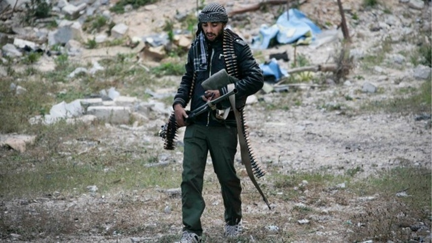April 23, 2011: A Libyan rebel fighter carries a heavy machine gun in the besieged city of Misrata, Libya.