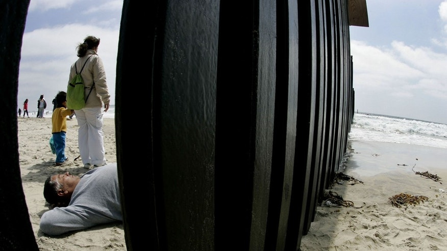 SAN YSIDRO, CA - JUNE 10:  A Mexican National lays out on the beach along the U.S. and Mexico border wall June 10, 2007 in San Ysidro, California. President Bush will meet with key Senators this week in an effort to persuade them to help pass his immigration reform package which would tighten borders, offer employers more temporary workers and provide lawful status to millions of illegal aliens.  (Photo by Sandy Huffaker/Getty Images)