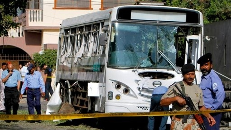 April 26: A Pakistani paramilitary soldier stands guard as Navy personnel examine a damaged bus at the site of a bomb blast in Karachi, Pakistan.