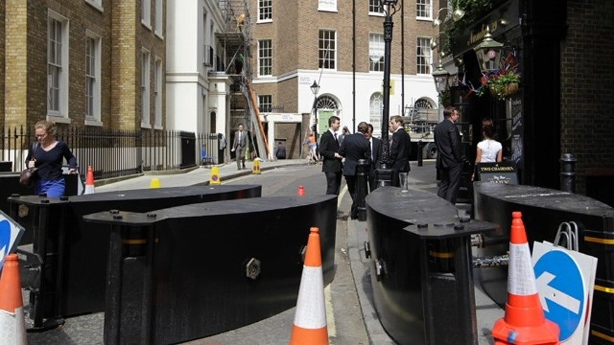 April 27, 2011: People mingle outside a pub on a street blocked off by security barriers near the Westminster Abbey in London in readiness for the royal wedding.