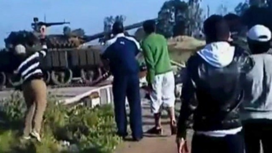 April 24: This video image taken from amateur video released by Sham News Network, a Syrian Freedom group, shows a man, left, preparing to throw an object at a tank as others look on, in Daraa, Syria.