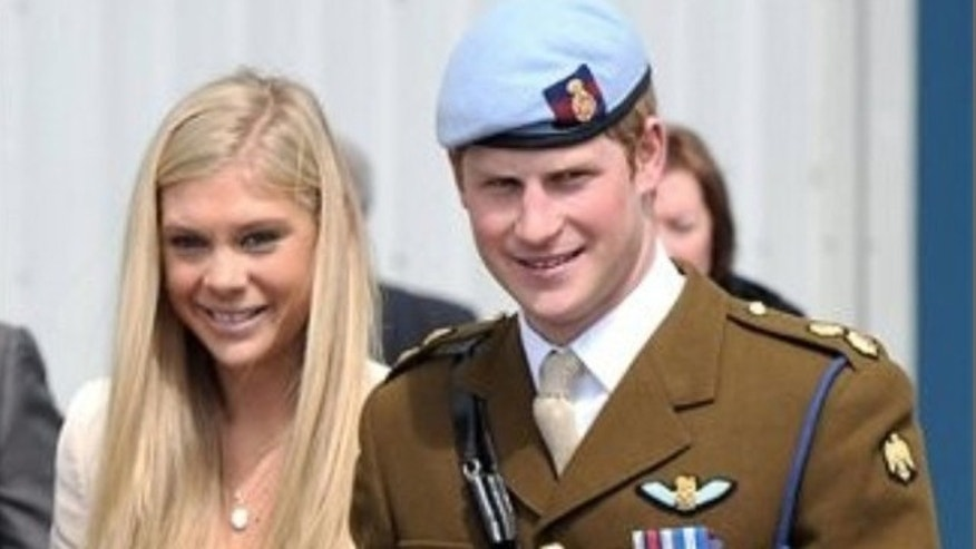 In this image made available by the Ministry of Defence in London, Britain's Prince Harry walks with his girlfriend Chelsy Davy after receiving his Helicopter Pilot's wings from his father, Prince Charles, in a graduation ceremony from an advanced helicopter training course at Middle Wallop, England, Friday May 7, 2010.