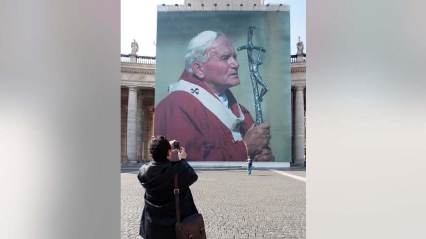 Faithful take a suovenir picture in front of a giant poster of late Pope John Paul II, in St. Peter's square, at the Vatican, April 28, 2011, days before John Paul's May 1 beatification. A prayer vigil on the Circus Maximus, an all-night prayer session in downtown Rome churches and the beatification Mass celebrated by Pope Benedict XVI top the agenda for the three-day event.
