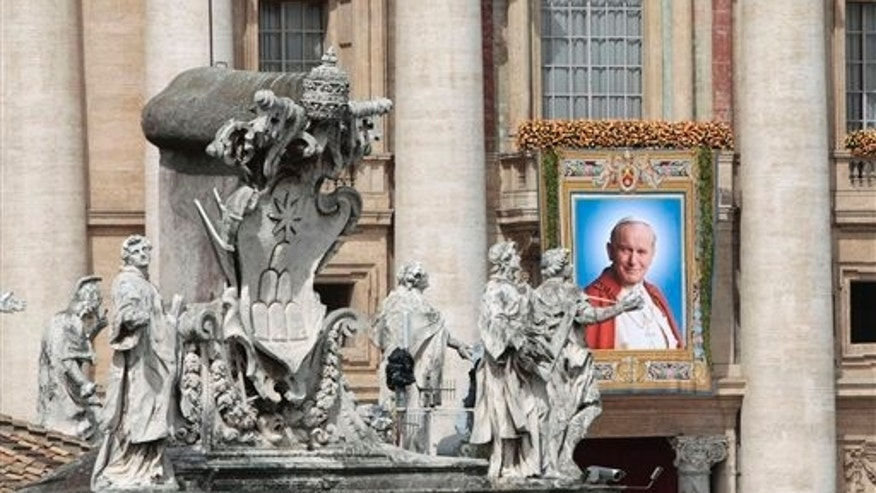 A tapestry of John Paul II is displayed on the facade of St. Peter's Basilica at the Vatican, Sunday, May 1, 2011. Pope Benedict XVI beatified Pope John Paul II before more than a million faithful in St. Peter's Square and surrounding streets Sunday, moving the beloved former pontiff one step closer to possible sainthood. (AP Photo/Gregorio Borgia)