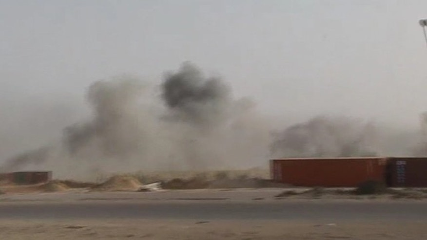 May 1: In this image taken from Associated Press Television News footage, smoke rises from the dock area of Misrata, Libya, after Libyan government forces fired more than two dozen Grad rockets and mortars towards the area. Misrata, which is the main rebel-held city in the west, has emerged as a key prize as the two sides have been locked in a stalemate with Qaddafi holding sway over the western half of the country and the rebels dominating the east. (AP/APTN)