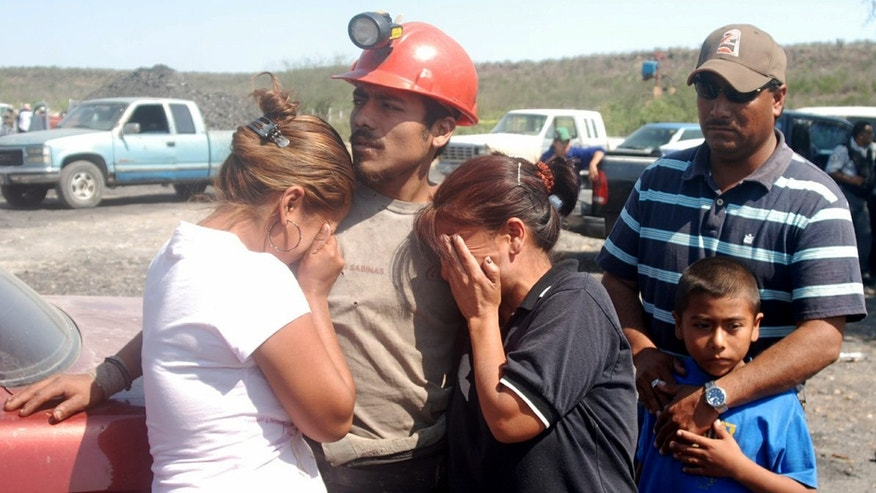 Family members of trapped miners embrace as they wait outside of a coal mine in San Juan de Sabinas, in the Mexican state of Coahuila, Tuesday, May 3, 2011. Authorities in northern Mexico said a gas explosion in the coal mine has trapped 14 miners. There are no deaths reported. (AP Photo/Grupo Zocalo, Sinhue Samaniego)