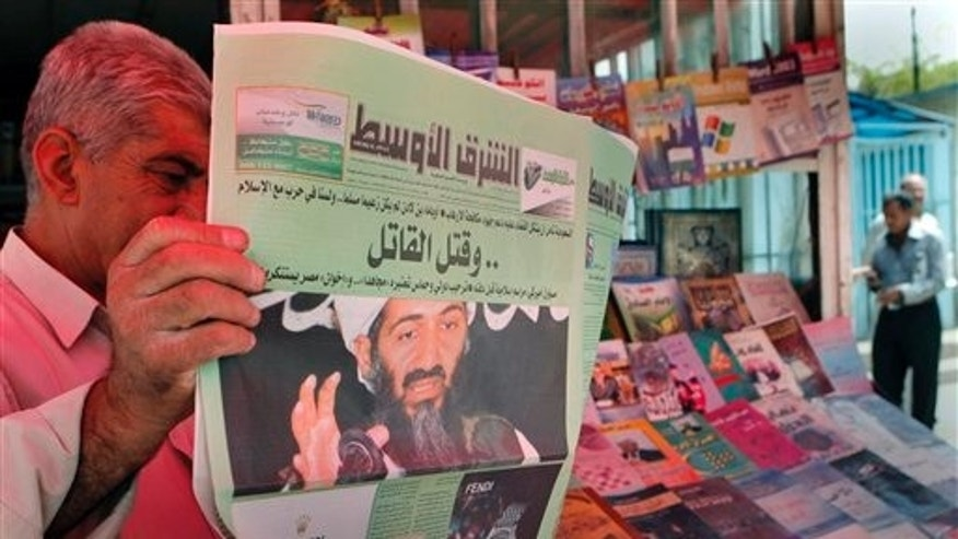 "May 3: An Iraqi man reads a newspaper with front page headlines reporting the killing of al-Qaida leader Osama bin Laden in Baghdad, Iraq. The news headline, in Arabic, reads: ""the Killer is killed."""