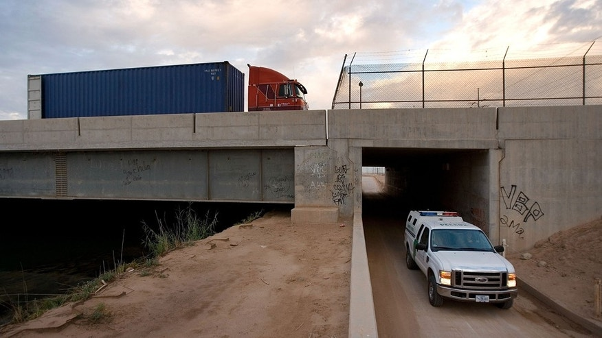 CALEXICO, CA - OCTOBER 03:  A truck passes into the US on the bridge over the All American Canal near a border patrol vehicle at Bond Crossing near to where new border fencing is proposed on October 3, 2007 east of Calexico, California. Many people have died swimming across the canal after crossing the border. Recent US federal construction of border fences has rapidly sped up. The sudden acceleration marks a change from a month ago when the Department of Homeland Security (DHS) announced that it would have only completed 15 of 70 miles of new fencing promised by the end of September, enraging anti-illegal-immigration groups and many Republicans. Instead, the DHS reached its goal of 70 miles to raise the total amount of border fences from 75 to about 145 miles. The fence-building frenzy is the result of the controversial Secure Fence Act, passed last fall, calling for 698 miles of border fences. Critics argue that extensive fencing will damage fragile desert environments, divide border neighborhoods, and that illegal immigrants will continue to find ways over, under, and through the fence or simply go around it elsewhere along the 2000-mile-long international border. Supporters believe that it will hinder border crossers.  (Photo by David McNew/Getty Images)