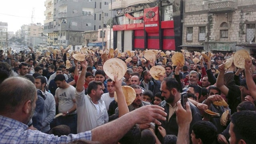 May 3: In this citizen journalism image made on a mobile phone and acquired by the AP, Syrian men carry bread loaves during a protest against Syrian President Bashar Assad's regime in the coastal town of Banias, Syria.