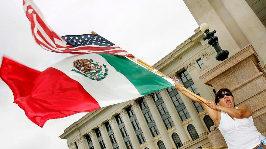 FILE - In this April 1, 2006 file photo, Patricia Gracia of Chihuahua, Mexico, waves American and Mexican flags at a Justice and Dignity for All Immigrants rally at the steps of the Oklahoma State Capital in Oklahoma City. New U.S. Census Bureau figures for Oklahoma, released Tuesday, Feb. 15, 2011, show that the state now has more residents who identify themselves as Hispanic than Native American. (AP Photo/Ty Russell, File)