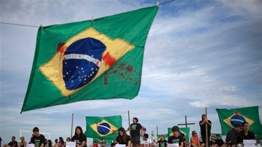 A Brazilian flag covered in red paint symbolizing blood hangs as people protest the trafficking of weapons and ammunition as a tribute to the victims at Tasso da Silveira school where a gunman shot and killed 12 children, on Copacabana Beach in Rio de Janeiro, Brazil, Sunday April 10, 2011. Ten girls and two boys between the ages of 12 and 15 were killed on Thursday by 23-year-old Wellington Oliveira, who shot and killed himself after being confronted by police. (AP Photo/Felipe Dana)