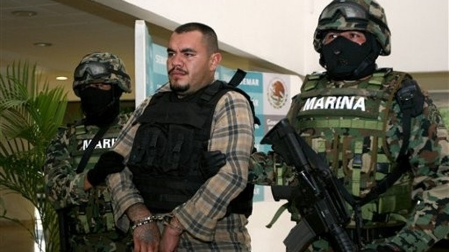 "Members of the Navy escort Martin Omar Estrada Luna, center, alias ""El Kilo,"" during a presentation to the press in Mexico City, Sunday, April 17, 2011. The Mexican Navy said Saturday it had captured Estrada Luna, the presumed leader of the San Fernando cell of the Zetas drug gang, suspected in the case of the mass graves found in Tamaulipas, as well as the migrant massacre last August in the violent border state across from Texas.  (AP Photo/Marco Ugarte)"
