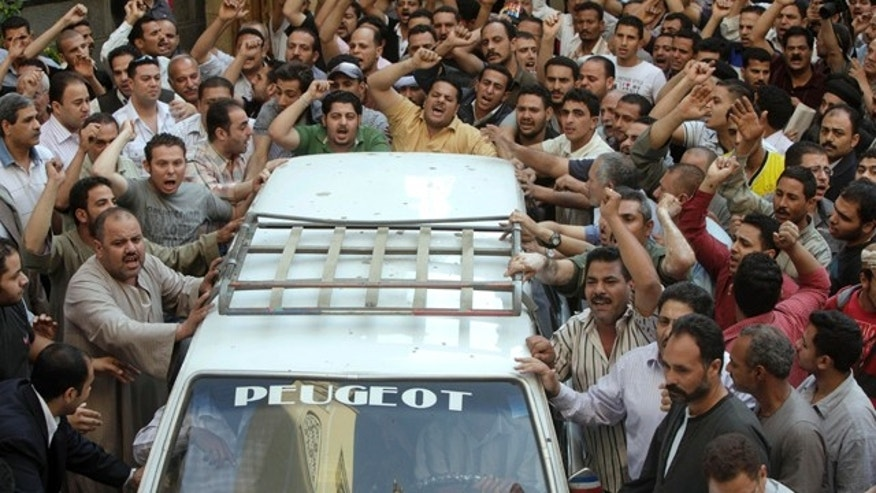May 8, 2011: Angry Egyptian Christians surround a coffin of one of the victims, of Saturday night clashes with Muslims in the streets of Imbaba western Cairo, during a funeral ceremony at Giza church. Muslim mobs set two Cairo churches on fire overnight during sectarian clashes that left 12 dead and more than 200 injured.