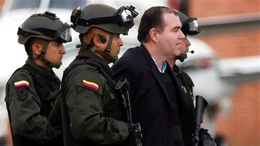 Colombian police officers escort alleged drug trafficker Walid The Turk Makled to a waiting plane at the military airport in Bogota, Colombia, Monday May 9, 2011. The Venezuelan citizen of Syrian descent was arrested late last year on a U.S. warrant in Colombia. Colombia President Juan Manuel Santos said the law favored Makled being sent to Venezuela instead of the U.S. because it was the first country to request his extradition.(AP Photo/Fernando Vergara)