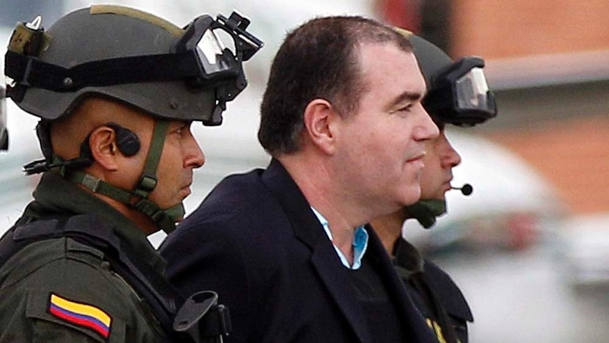 "Colombian police officers escort alleged drug trafficker Walid ""The Turk"" Makled to a waiting plane at the military airport in Bogota, Colombia, Monday May 9, 2011. The Venezuelan citizen of Syrian descent was arrested late last year on a U.S. warrant in Colombia. Colombia President Juan Manuel Santos said the law favored Makled being sent to Venezuela instead of the U.S. because it was the first country to request his extradition.(AP Photo/Fernando Vergara)"
